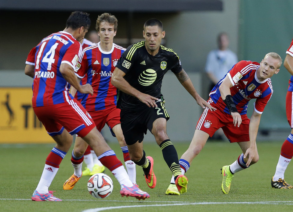 Photo - Seattle Sounders midfielder Clint Dempsey, center, tries to get the ball past Bayern Munich's Claudio Pizarro (14) in the first half of the MLS All-Star soccer game Wednesday, Aug. 6, 2014, in Portland, Ore. (AP Photo/Ted S. Warren)