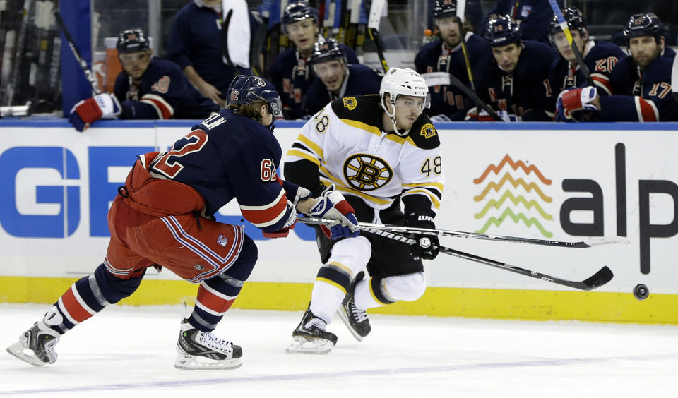 Photo - New York Rangers left wing Carl Hagelin (62) and Boston Bruins left wing Chris Bourque (48) chase the puck in the first period of their NHL hockey game at Madison Square Garden in New York, Wednesday, Jan. 23, 2013.  (AP Photo/Kathy Willens)