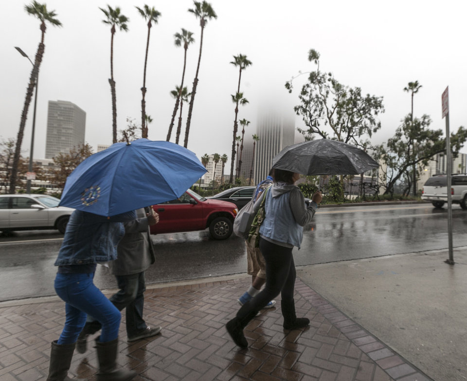 Heavy fog obscures the tops of buildings as pedestrians pass by in a rainstorm Friday Nov. 30, 2012 in Los Angeles. A series of storm systems will continue to move across southwestern Calif.,  through Monday morning. (AP Photo/Damian Dovarganes)