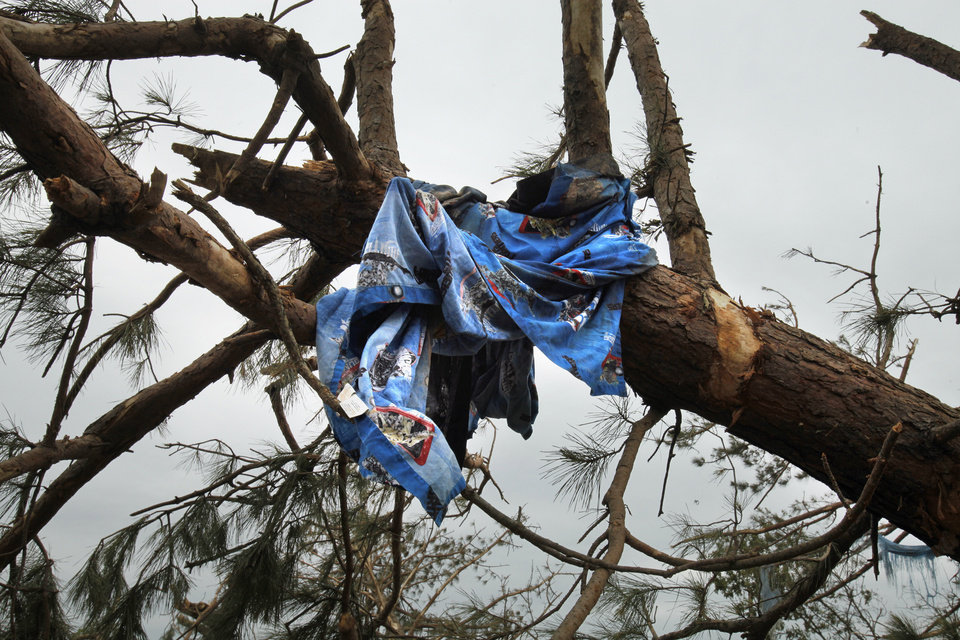 Photo - A child's blanket is caught in a tree on the hillside north of Highway 9 near SE 192 on Wednesday, May 12, 2010, in Norman, Okla.   A mother died and her children were injured at this location during Monday's severe storms.  Photo by Steve Sisney, The Oklahoman