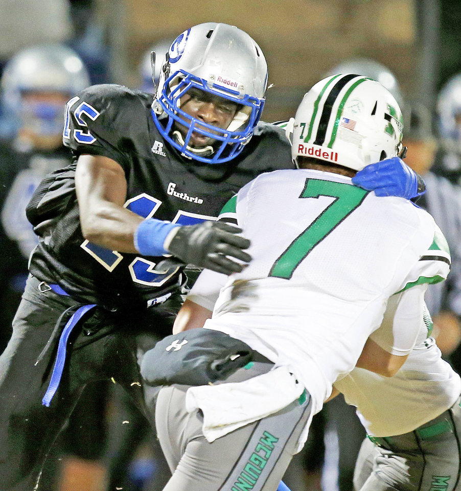 Guthrie's L'Liott Curry, left, brings down Bishop McGuinness' Jacob Lewis during a game in Guthrie. Photo by Bryan Terry, The Oklahoman