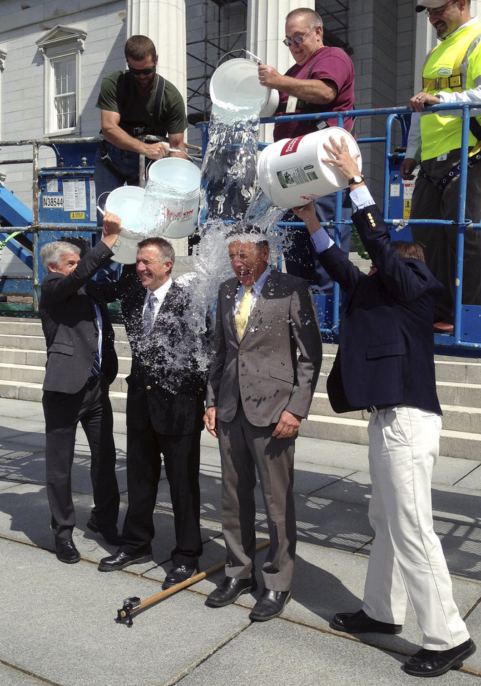 "Photo - Vermont Lt. Gov. Phil Scott, second from left, and Gov. Peter Shumlin, second from right, take the ""ice bucket challenge"" at the Vermont Statehouse Thursday, Aug. 14, 2014, in Montpelier, Vt. They were doused by Montpelier Mayor John Hollar, left, Barre Mayor Thom Lauzon, right, and a team of dousers working from a crane above. The challenge is aimed at raising funds to fight ALS, also known as Lou Gehrig's disease. (AP Photo/Dave Gram)"