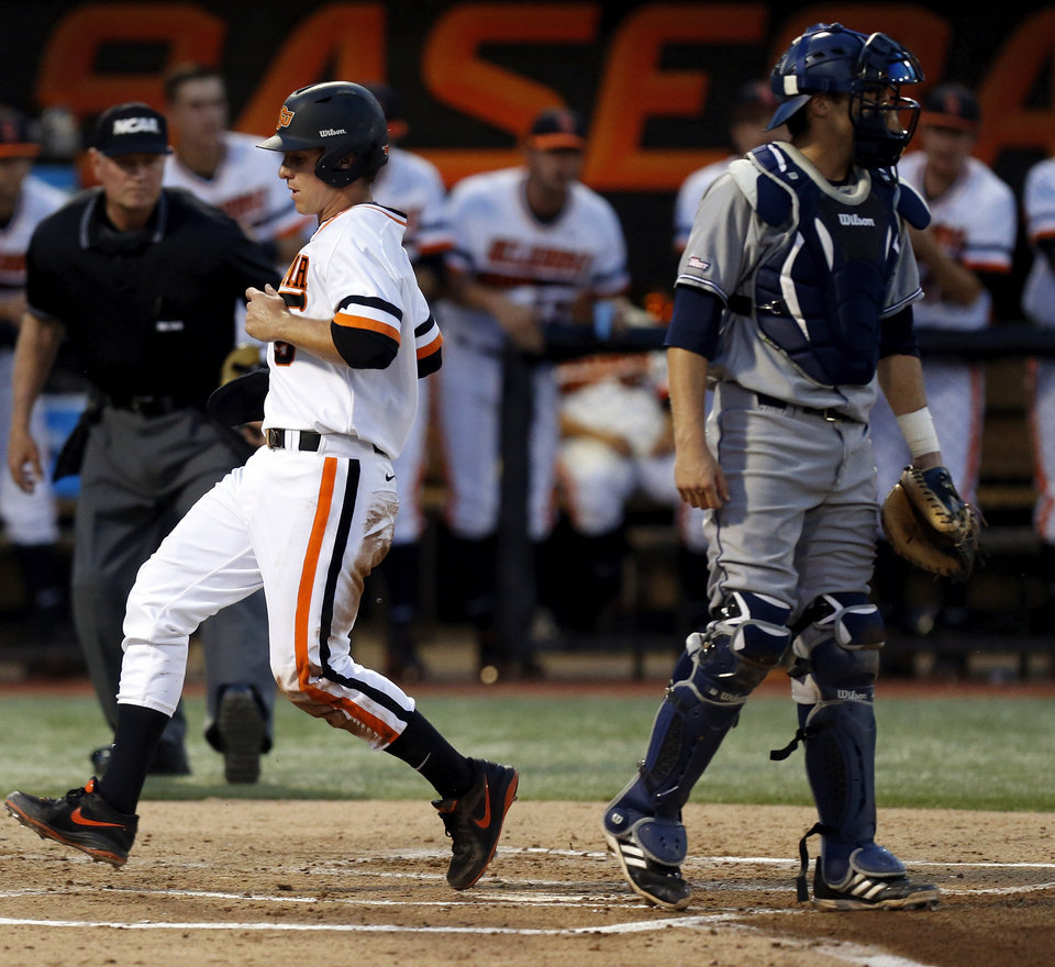 Photo - OSU's Donnie Walton (5) scores past UC Irvine's Jerry McClanahan (11) in the first inning during Game 1 of the NCAA baseball Stillwater Super Regional between Oklahoma State and UC Irvine at Allie P. Reynolds Stadium in Stillwater, Okla., Friday, June 6, 2014. Photo by Nate Billings, The Oklahoman