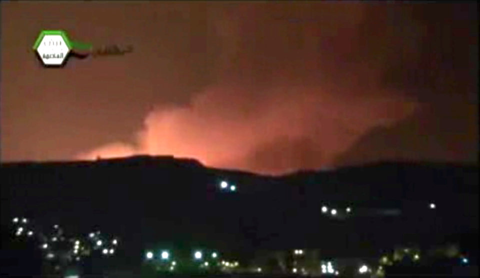 Photo - In this image taken from video obtained from the Ugarit News, which has been authenticated based on its contents and other AP reporting, smoke and fire fill the the skyline over Damascus, Syria, early Sunday, May 5, 2013 after an Israeli airstrike. Israeli warplanes struck areas in and around the Syrian capital Sunday, setting off a series of explosions as they targeted a shipment of highly accurate, Iranian-made guided missiles believed to be on their way to Lebanon's Hezbollah militant group, officials and activists said. The attack, the second in three days, signaled a sharp escalation of Israel's involvement in Syria's bloody civil war. Syria's state media reported that Israeli missiles struck a military and scientific research center near the Syrian capital and caused casualties. (AP Photo/Ugarit News via AP video)