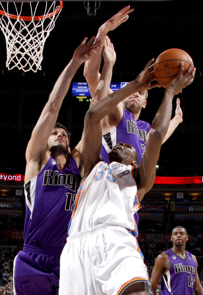 Photo - Oklahoma City's Kevin Durant goes to the basket between Sacramento's Omri Casspi, left, and Spencer Hawes during the NBA basketball game between the Oklahoma City Thunder and the Sacramento Kings at the Ford Center in Oklahoma City, Tuesday, March 2, 2010.  Photo by Bryan Terry, The Oklahoman