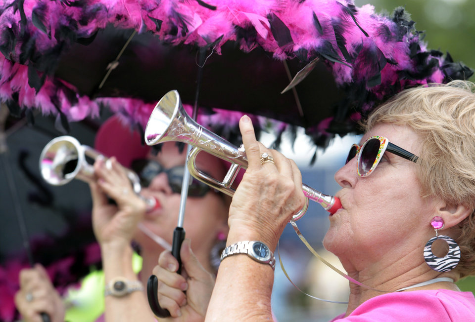 Photo -   Barbara Hammett, right, and Janet Larue, both of Metairie, play toy trumpets as they watch from the crowd as The New Orleans Classic Review featuring Frankie Ford, Al