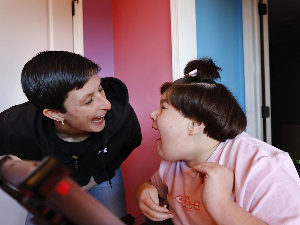 Photo -  Amy Melton and daughter, Brittany, who has developmental disabilities, play a game at their newly built house in Ada, which they might not move into.    Jim Beckel -