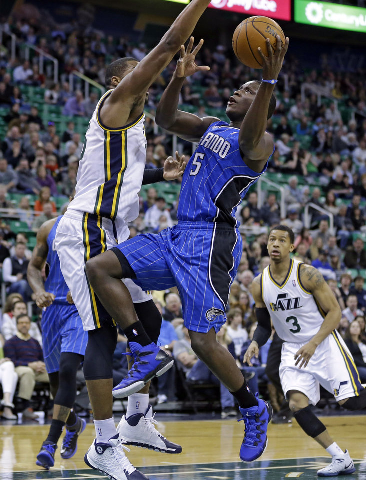 Photo - Utah Jazz's Derrick Favors, left, defends against Orlando Magic's Victor Oladipo (5) who goes to the basket as Utah Jazz's Trey Burke (3) looks on in the first quarter during an NBA basketball game on Saturday, March 22, 2014, in Salt Lake City. (AP Photo/Rick Bowmer)