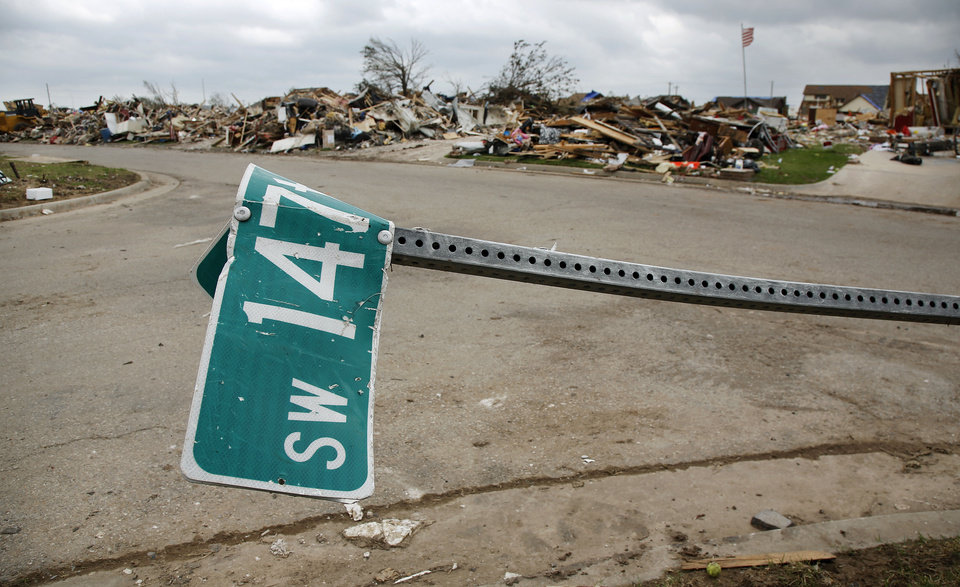 A street sign lies over the street on SW 147 in the Westmoor Addition Wednesday. Oklahoma City, like most other metro cities, has no public storm shelters. <strong>Jim Beckel - THE OKLAHOMAN</strong>