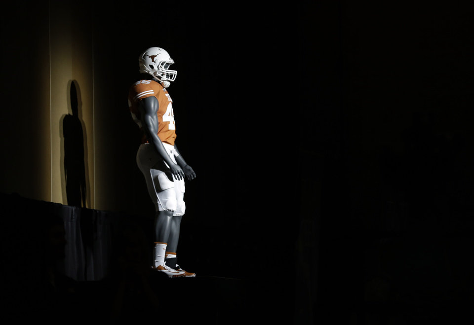 Photo - A mannequin with dressed in a University of Texas uniform is displayed in the darkened hotel ballroom hosting the Big 12 Conference NCAA college football media days in Dallas, Tuesday, July 22, 2014. (AP Photo)