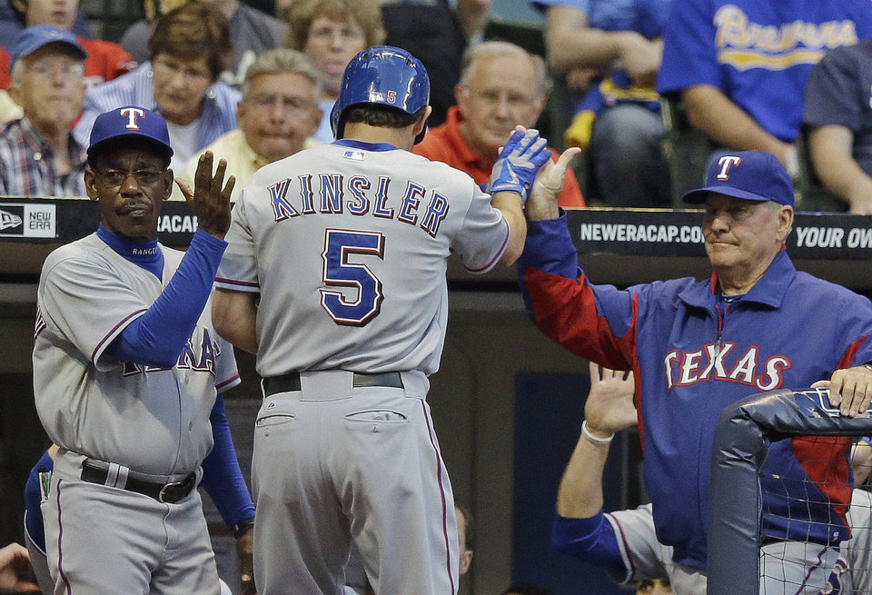 Photo - Texas Rangers' Ian Kinsler (5) is congratulated after hitting a home run during the second inning of a baseball game against the Milwaukee Brewers Wednesday, May 8, 2013, in Milwaukee. (AP Photo/Morry Gash)
