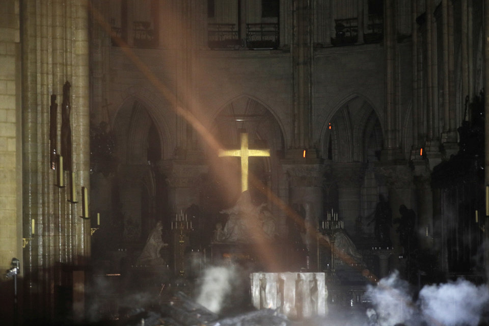 Photo - Smoke is seen around the alter inside Notre Dame cathedral in Paris, Monday, April 15, 2019. A catastrophic fire engulfed the upper reaches of Paris' soaring Notre Dame Cathedral as it was undergoing renovations Monday, threatening one of the greatest architectural treasures of the Western world as tourists and Parisians looked on aghast from the streets below. (Philippe Wojazer/Pool via AP)