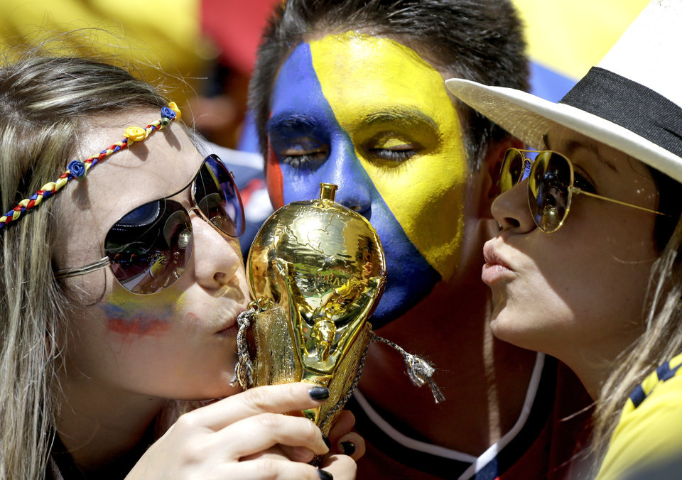 Colombian supporters kiss a replica of the World Cup trophy before the group C World Cup soccer match between Colombia and Ivory Coast at the Estadio Nacional in Brasilia, Brazil, Thursday, June 19, 2014. (AP Photo/Sergei Grits)