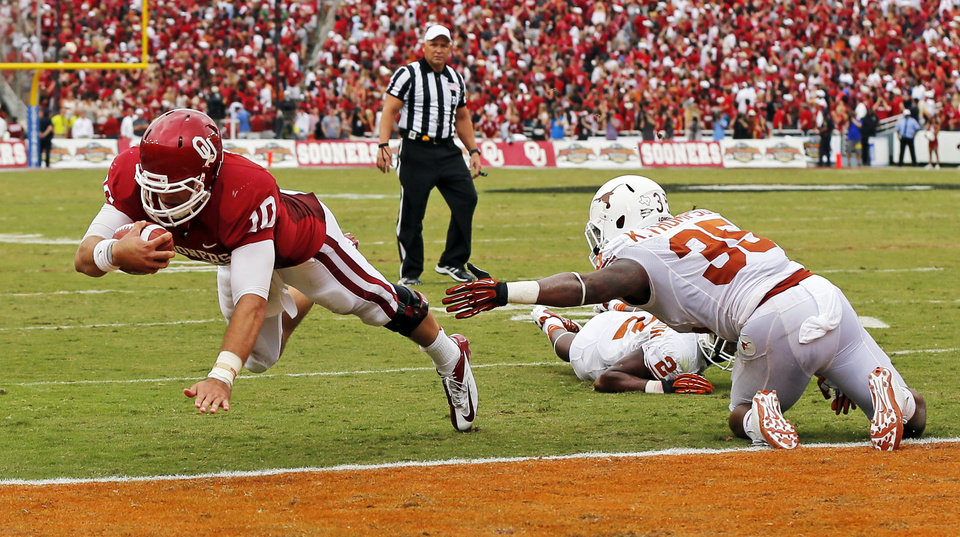 Photo - OU's Blake Bell (10) dives for a touchdown past UT's Kendall Thompson (35) in the second quarter during the Red River Rivalry college football game between the University of Oklahoma (OU) and the University of Texas (UT) at the Cotton Bowl in Dallas, Saturday, Oct. 13, 2012. Photo by Nate Billings, The Oklahoman