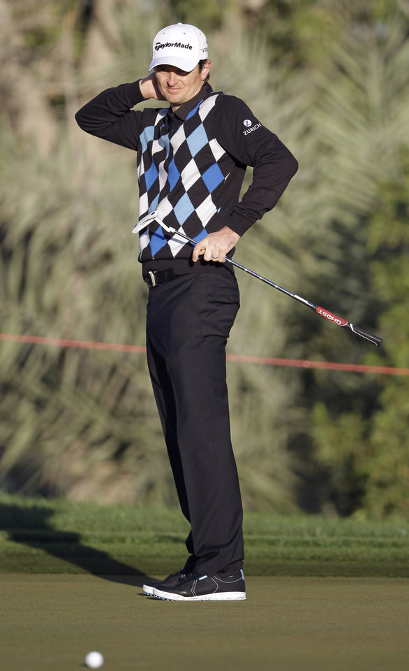 Justin Rose of England reacts after he missed a putt on the 10th hole during the second round of Abu Dhabi Golf Championship in Abu Dhabi, United Arab Emirates, Friday, Jan. 18, 2013. (AP Photo/Kamran Jebreili)