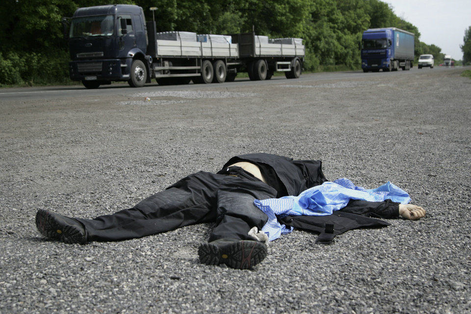 Photo - A body of a Ukrainian national guard member lies on a road in the village of Karlivka, some 40 kilometers (25 miles) west of the city of Donetsk, eastern Ukraine, on Friday May 23, 2014.  At least three people died when Ukrainian national guard unit and pro-Russian militiamen fought in the village of Karlivka early Friday. (AP Photo/Alexander Ermochenko)