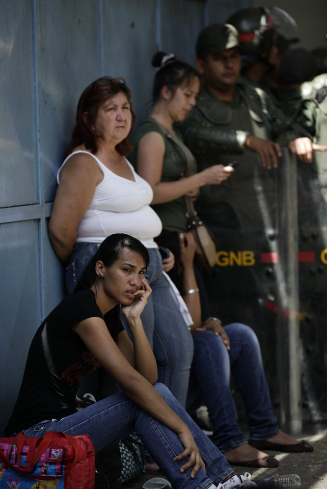 Photo -   Inmate's relatives wait outside La Planta prison in Caracas, Venezuela, Saturday, April 28, 2012. Hundreds of inmate's relatives were not allowed to enter for normal visiting hours because they were canceled after authorities foiled plans for a prison break on Friday. Venezuelan authorities say they discovered a tunnel that inmates had dug leading to a sewer. (AP Photo/Ariana Cubillos)
