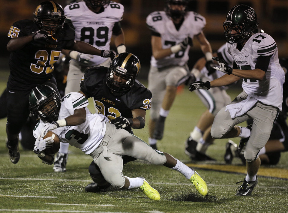 Norman North\'s Bryan Payne (3) is taken down by Midwest City\'s Meli Brewer (22) during a high school football game between Midwest City and Norman North in Midwest City, Friday, Sept. 21, 2012. Photo by Garett Fisbeck, The Oklahoman