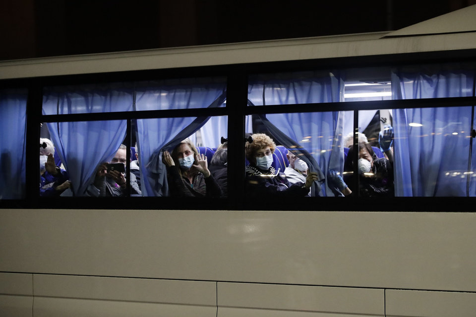 Photo -  Buses carrying passengers from the quarantined Diamond Princess cruise ship leave a port in Yokohama, near Tokyo, Monday, Feb. 17, 2020. A group of Americans are cutting short a 14-day quarantine on the Diamond Princess cruise ship in the port of Yokohama, near Tokyo, to be whisked back to America. But they will have to spend another quarantine period at a U.S. military facility to make sure they don't have the new virus that's been sweeping across Asia. (AP Photo/Jae C. Hong)