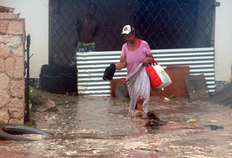 Photo -   A woman wades through flood water brought by Hurricane Sandy as she evacuates her home in the Caribbean Terrace neighborhood of eastern Kingston, Jamaica, Wednesday, Oct. 24, 2012. Hurricane Sandy pounded Jamaica with heavy rain as it headed for landfall near the country's most populous city on a track that would carry it across the Caribbean island to Cuba, and a possible threat to Florida. (AP Photo/Collin Reid)