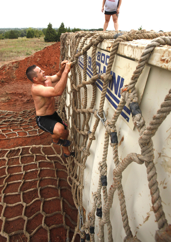 Luke Gregory climbs a cargo net during the Juggernaut mud run at Mitch Park, in Edmond, OK, Saturday, September 29, 2012. The Juggernaut is part of a national mud run series to raise money for Susan G. Komen for the Cure. By Paul Hellstern, The Oklahoman