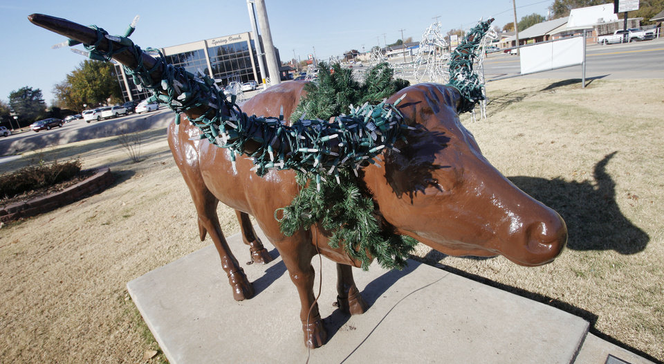 Photo - A Texas longhorn statue with Christmas lights strung on its  antlers and a wreath around its  neck us at the entrance to Chisholm Trail Park for the Christmas in the Park light show in Yukon. Photo by Paul B. Southerland, The Oklahoman  PAUL B. SOUTHERLAND - PAUL B. SOUTHERLAND