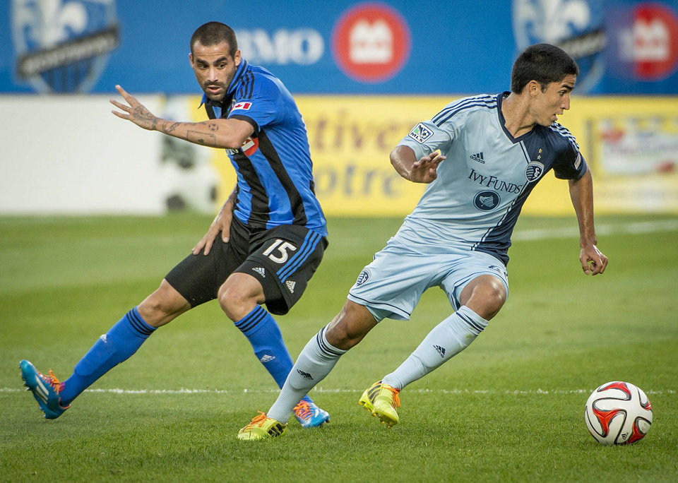 Photo - Sporting Kansas City' Igor Juliao, right, steals the ball away from Montreal Impact's Andres Romero during the first half of a soccer game, Saturday, July 12, 2014 in Montreal. (AP Photo/The Canadian Press, Peter McCabe)