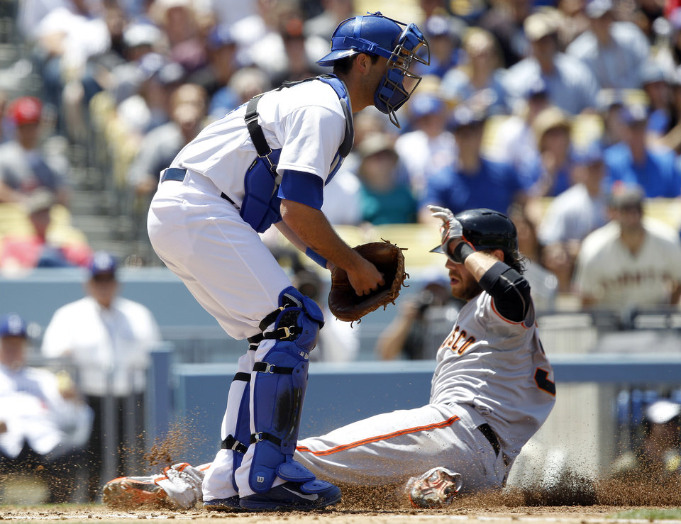 Photo - San Francisco Giants' Brandon Crawford, right, slides into home to beat the throw to Los Angeles Dodgers catcher Drew Butera, left, to score on a sacrifice fly hit by Giants' Hunter Pence in the second inning of a baseball game on Saturday, May 10, 2014, in Los Angeles. (AP Photo/Alex Gallardo)