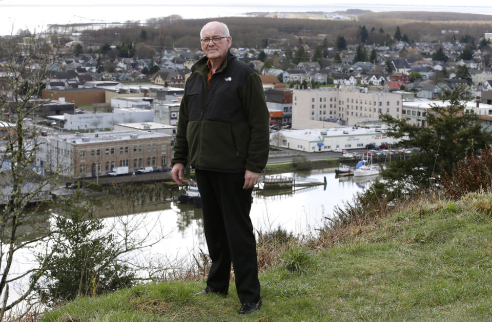 Photo - Jack Durney, mayor of Hoquiam, Wash., stands on a hill on Monday, March 18, 2014, overlooking his city, the Hoquiam River, and Grays Harbor. Because most of Hoquiam lies in the flood plain, Durney says possible increases in federal flood insurance rates would adversely affect many who live in his town. In the old logging port on an estuarine bay, the great majority of the 8,700 residents live in a flood hazard area. (AP Photo/Ted S. Warren)