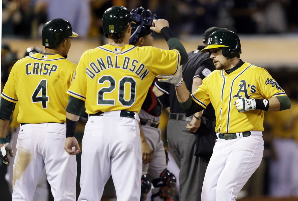 Oakland Athletics' Jed Lowrie, right, reaches home plate after driving in Josh Donaldson (20) and Coco Crisp (4) with a three-run home run against the Minnesota Twins during the sixth inning of a baseball game on Thursday, Sept. 19, 2013, in Oakland, Calif. (AP Photo/Marcio Jose Sanchez)