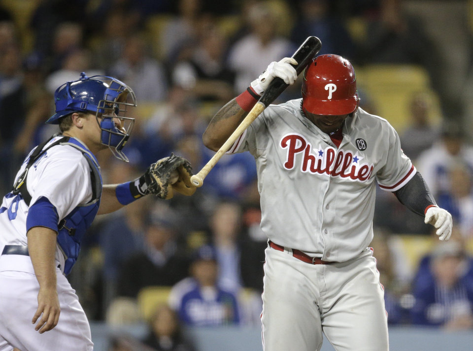 Photo - Philadelphia Phillies' Marlon Byrd, right, hits himself with a bat after striking out as Los Angeles Dodgers catcher Tim Federowicz walks toward the dugout during the ninth inning of a baseball game against the Los Angeles Dodgers on Tuesday, April 22, 2014, in Los Angeles. (AP Photo/Jae C. Hong)