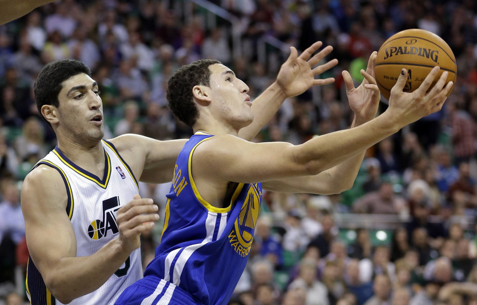 Photo - Golden State Warriors' Klay Thompson, right,  grabs a rebound as Utah Jazz's Enes Kanter, left, of Turkey, looks on in the fourth quarter during an NBA basketball game Monday, Nov. 18, 2013, in Salt Lake City. (AP Photo/Rick Bowmer)