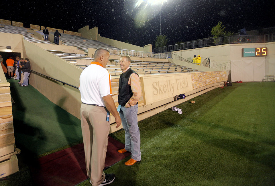 Photo - Oklahoma State University athletic director Mike Holder stands on the sidelines as the stadium is cleared due to storms before the start of college football game between the Oklahoma State University Cowboys and the University of Tulsa Golden Hurricane at H.A. Chapman Stadium in Tulsa, Okla., Saturday, Sept. 17, 2011. Photo by Chris Landsberger, The Oklahoman