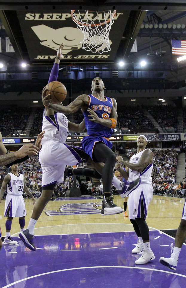 New York Knicks guard J.R.Smith, center, drives to the basket between  Sacramento Kings' Jason Thompson, left,and James Johnson, right, during the first quarter of an NBA basketball game in Sacramento, Calif., Friday, Dec. 28, 2012.(AP Photo/Rich Pedroncelli)