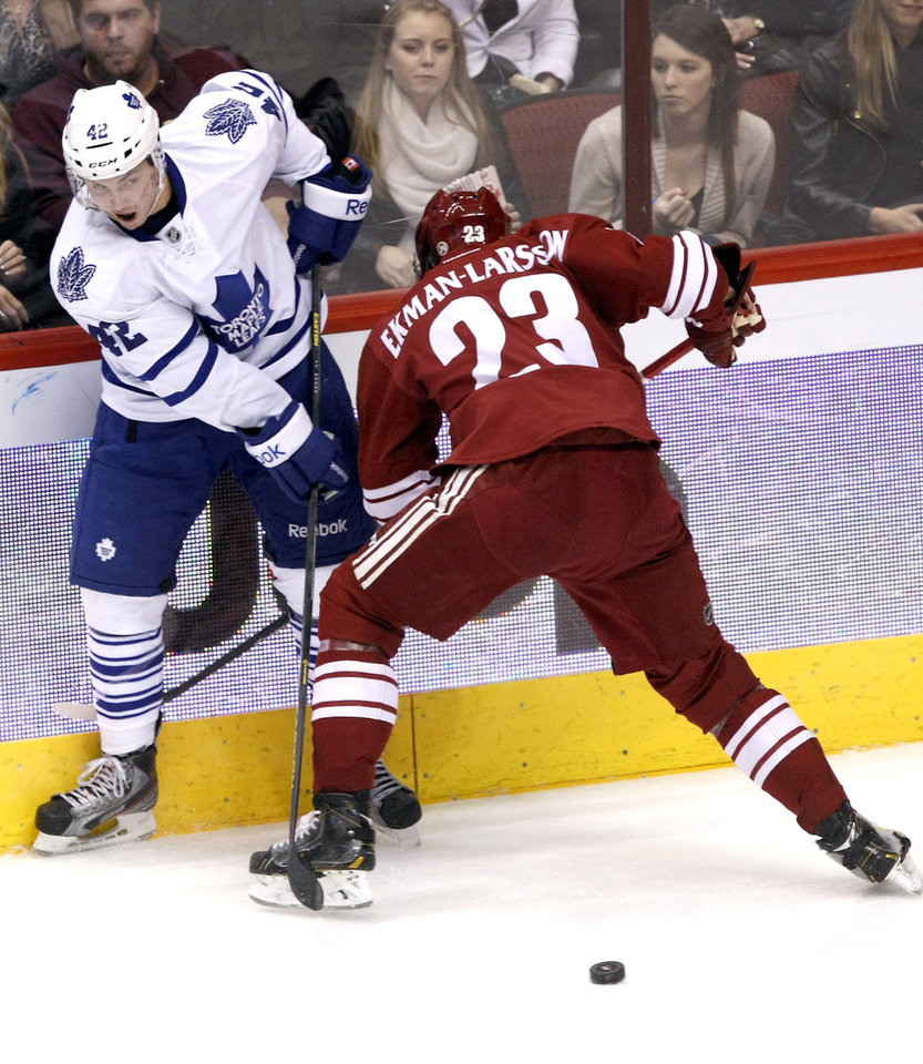 Photo - Toronto Maple Leafs center Tyler Bozak (42) and Phoenix Coyotes defenseman Oliver Ekman-Larsson (23) battle for the puck in the second period of an NHL hockey game, Monday, Jan. 20, 2014, in Glendale, Ariz. (AP Photo/Rick Scuteri)