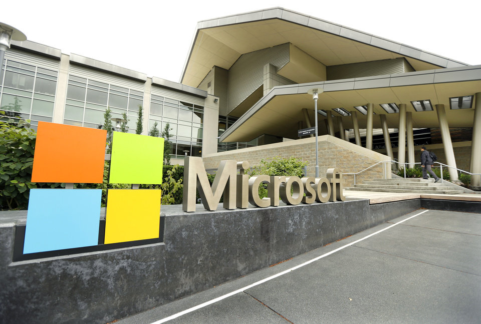 Photo - This July 3, 2014 photo shows Microsoft Corp. signage outside the Microsoft Visitor Center in Redmond, Wash. Microsoft on Thursday, July 17, 2014 announced it will lay off 18,000 workers over the next year. (AP Photo Ted S. Warren)