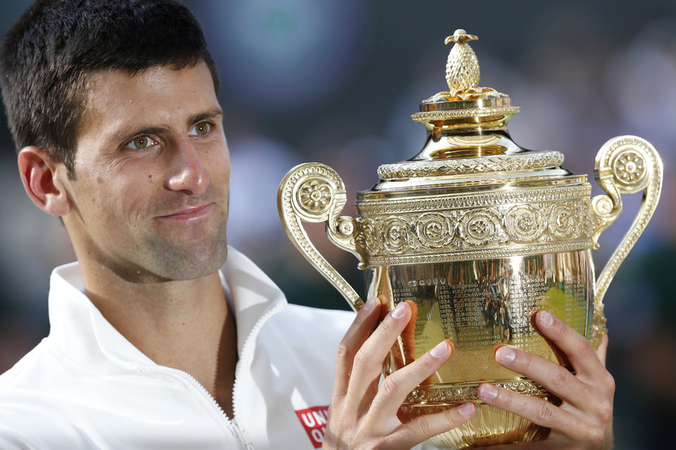 Photo - Novak Djokovic of Serbia holds the trophy after defeating Roger Federer of Switzerland in the men's singles final at the All England Lawn Tennis Championships in Wimbledon, London, Sunday July 6, 2014. (AP Photo/Ben Curtis)