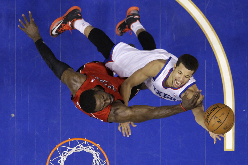 Photo - Philadelphia 76ers' Michael Carter-Williams, right, goes up for a shot against Toronto Raptors' Patrick Patterson during the second half of an NBA basketball game, Friday, Jan. 24, 2014, in Philadelphia. The Raptors won 104-95. AP Photo/Matt Slocum)