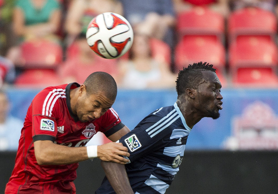 Photo - Toronto FC defender Justin Morrow, left, heads the ball past Sporting Kansas City C.J. Sapong during the first half of an MLS soccer game Saturday, July 26, 2014, in Toronto. (AP Photo/The Canadian Press, Nathan Denette)