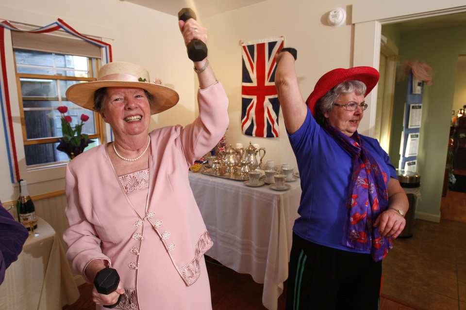 Photo - Wendy Mahoney, left, and Cecille Gregoire lift dumbbells as they exercise at Age Right Fitness in Hallowell, Maine, while watching the wedding of Britain's Prince William and Kate Middleton on a television Friday, April 29, 2011. The club held a royal wedding viewing party for it's members.(AP Photo/Robert F. Bukaty) ORG XMIT: MERB102
