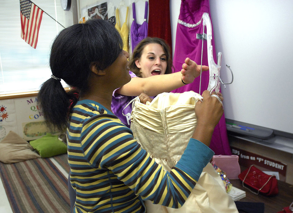 Photo -   In this photo taken Oct. 2, 2012 in Bloomington, Ill., Kiara Cross, 16, a junior, left, and Ginny McElwain, 17, a senior, have fun setting up prom dresses at Bloomington High School's House of Style. The House of Style started four years ago when advisor McElwain, urged a student to go to the prom who said she couldn't afford a dress. McElwain was not deterred by the students predicament and got the girl a dress and she went to the dance. Since then McElwain and various volunteers have given away 370 dresses to BHS students for homecoming and prom dances, even weddings. (AP Photo/The Pantagraph, David Proeber)
