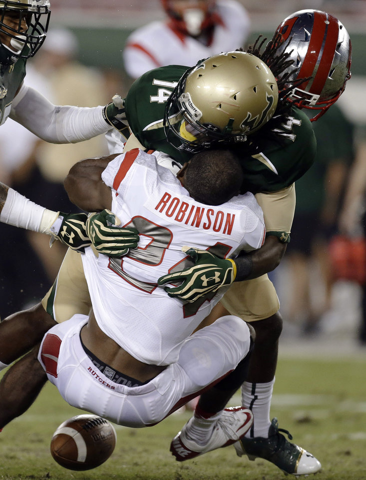 Photo -   Rutgers' Mason Robinson (24) loses the football and his helmet after a hit by South Florida's Fidel Montgomery (14) and another South Florida after fielding a punt during the first quarter of an NCAA college football game Thursday, Sept. 13, 2012, in Tampa, Fla. South Florida recovered the fumble. (AP Photo/Chris O'Meara)
