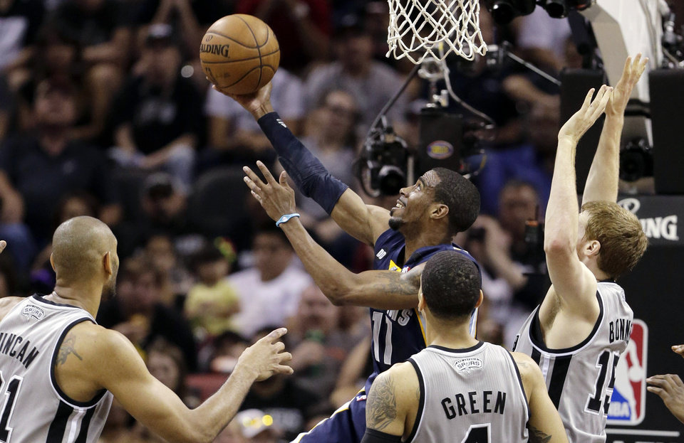 Photo - Memphis Grizzlies' Mike Conley (11) shoots as San Antonio Spurs' Tim Duncan, left, Danny Green, and Matt Bonner, right, defend him during the first half in Game 1 of a Western Conference Finals NBA basketball playoff series, Sunday, May 19, 2013, in San Antonio. (AP Photo/Eric Gay)
