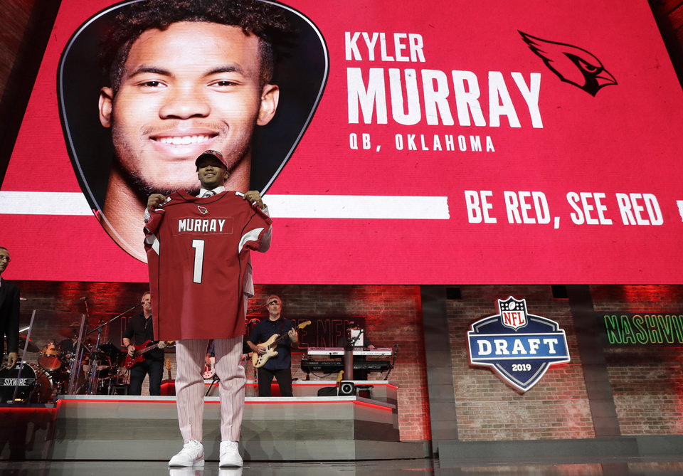 Photo - Oklahoma quarterback Kyler Murray shows off his new jersey after the Arizona Cardinals selected Murray in the first round at the NFL football draft, Thursday, April 25, 2019, in Nashville, Tenn. (AP Photo/Mark Humphrey)