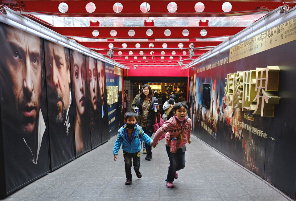 In this Feb. 7, 2013 photo, movie goers head to a popular theater complex as the Chinese New Year nears in Taipei, Taiwan. Tens of millions of film fanatics are entering theaters around Asia during the long Lunar New Year holiday, but Hollywood can�t count on them to boost the box office for its mostly serious Oscar nominees. Even with the Academy Awards buzz at a peak barely two weeks before the ceremony, patrons are opting for lighter fare. (AP Photo/Wally Santana)