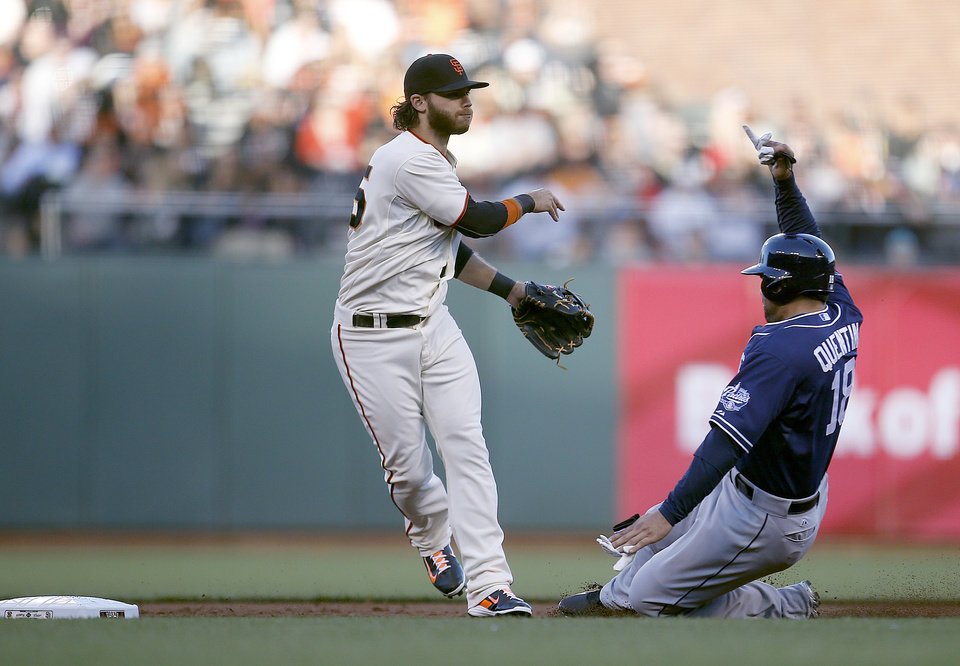 Photo - San Francisco Giants shortstop Brandon Crawford (35) forces San Diego Padres' Carlos Quentin (18) at second base and relays the throw to first base to turn double play on Yasmani Grandal during the second inning of a baseball game in San Francisco, Monday, June 23, 2014. (AP Photo/Tony Avelar)