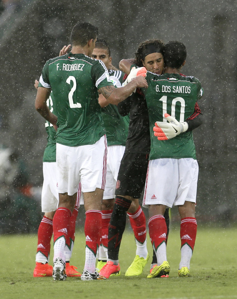 Photo - Mexico's Francisco Rodriguez (2) and Giovani dos Santos (10) congratulate their goalkeeper Guillermo Ochoa following their 1-0 victory over Cameroon in the group A World Cup soccer match between Mexico and Cameroon in the Arena das Dunas in Natal, Brazil, Friday, June 13, 2014.  (AP Photo/Petr David Josek)