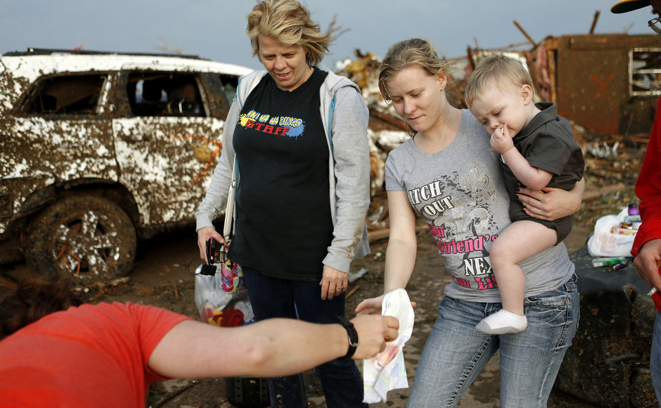 Tammy Preston holds her son Landon Wingate, 21 months, as she is handed diapers beside her mother Linda Preston, left, in Moore, Okla., after a tornado moved through the area on Monday, May 20, 2013. The family took shelter in a closet inside their home as it was damaged by a tornado. Photo by Bryan Terry, The Oklahoman