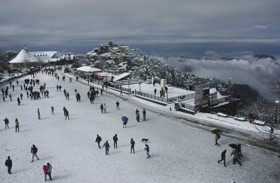 People walk after a snowfall in Shimla, Himachal Pradesh state, India, Wednesday, Feb. 6, 2013. According to the Press Trust of India, five persons were missing and three others were injured when an avalanche hit a cluster of houses in Kafnu village, about 190 kilometers (119 miles) from Shimla. (AP Photo/Mainka Gill)