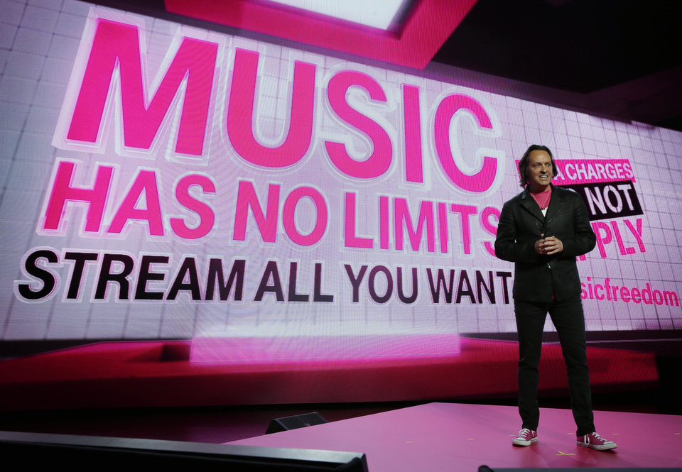 Photo - T-Mobile CEO John Legere talks about a new music streaming service at T-Mobile's Uncarrier 5.0 event, Wednesday, June 18, 2014, in Seattle. (AP Photo/Ted S. Warren)